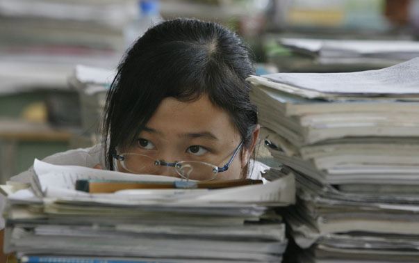 A middle school student sits behind a pile of books and notes in Anxian