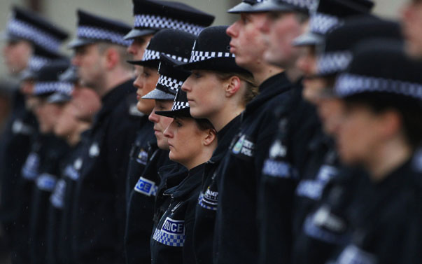 Police recruits stand to attention during their passing out parade at the Scottish Police College in Tulliallan, Scotland