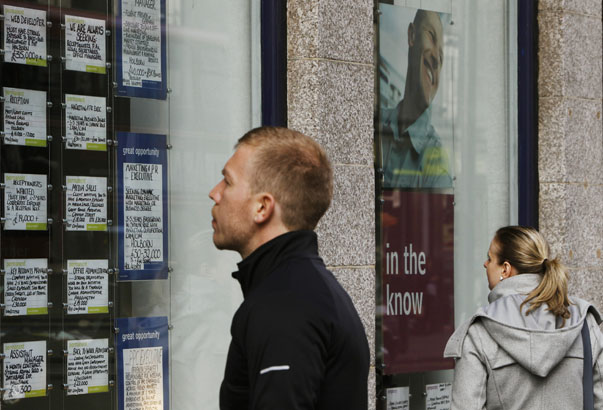 People look at adverts posted in the window of a recruitment agency in London