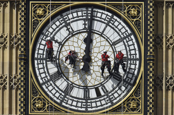 Cleaners abseil down one of the faces of Big Ben, to clean and polish the clock face, above the Houses of Parliament, in central London