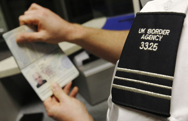 A UK Border Agency worker poses with a passport during a demonstration of the new facial recognition gates at Gatwick Airport near London