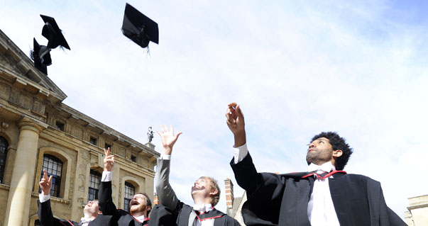 A group of graduates throw their caps in the air for a photograph after a graduation ceremony at Oxford University England