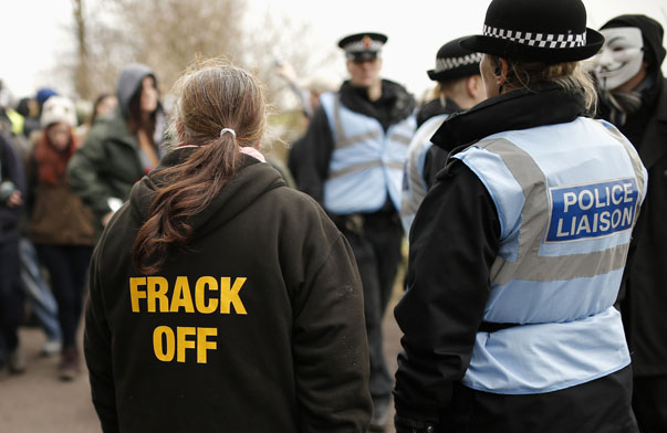 A protestor stands with police officers near to the entrance of the IGas exploratory gas drilling site at Barton Moss, near Manchester