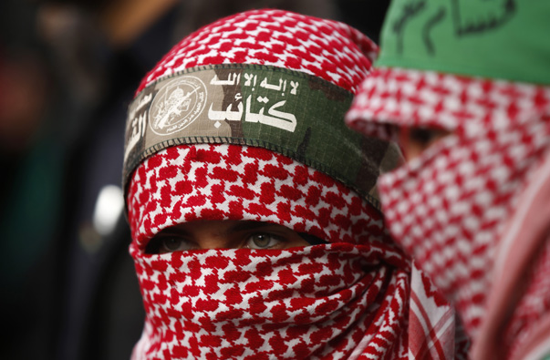 Masked Palestinian girls watch as Palestinian members of al-Qassam Brigades take part in a military parade in Gaza City