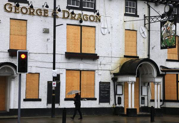A woman walks past a closed down pub near Manchester