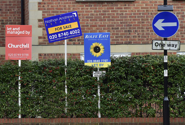Property sale and rental signs are seen next to a street sign in London
