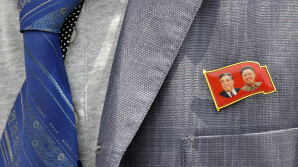 A participant wears a badge showing former North Korean leaders Kim Il Sung and Kim Jong Il during the opening ceremony of a new dock at the port of Rajin