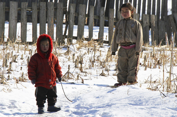 North Korean children stand after snowfall along the banks of the Yalu River, near the North Korean Sakchu County