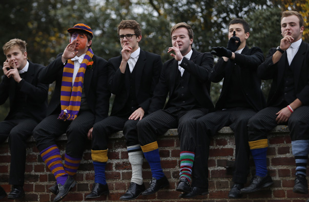 Etonians sit on the wall and react as the Collegers and the Oppidans teams compete during the Eton Wall Game at Eton college in Eton