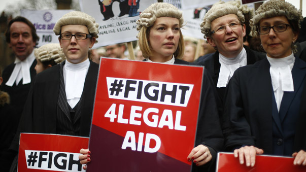 Barristers in their wigs and robes carry placards during a protest against cuts to the legal aid budget outside Parliament in central London
