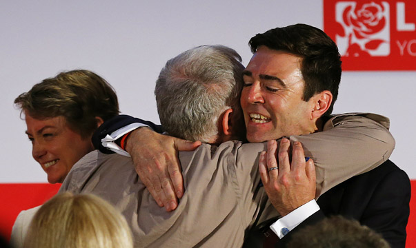 Labour Party leadership candidates Jeremy Corbyn and Andy Burnham embrace as Yvette Cooper walks off stage after a hustings event in Stevenage