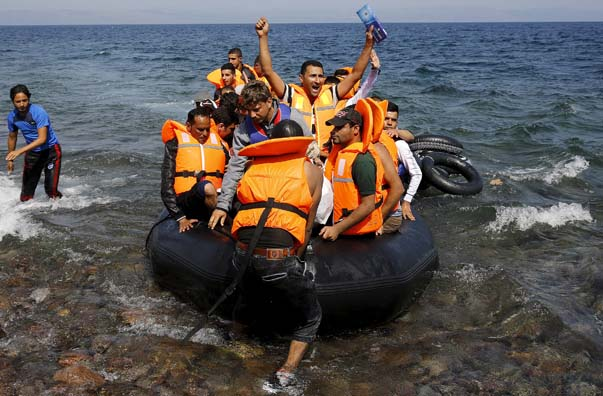 A Syrian refugee reacts in an overcrowded dinghy after landing safely on the Greek island of Lesbos