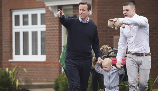 Britain's Prime Minister David Cameron, speaks to first-time buyer Robert Arron and 1-year old Finlay during a general election campaign visit to a housing development in Chorley, England