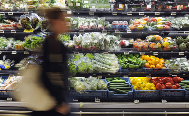 A customer walks pass the fruit and vegetable department of a Carrefour grocery store in Brussels
