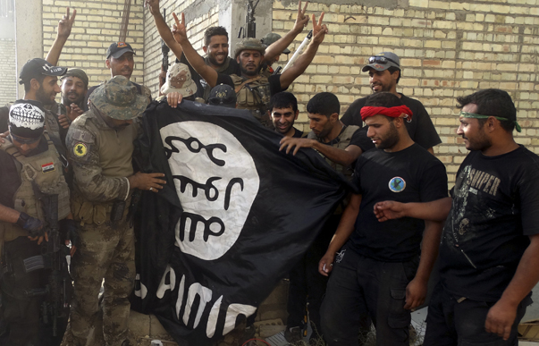 Iraqi security forces stand with an Islamist State flag which they pulled down at the University of Anbar, in Anbar province July 26, 2015. Iraqi security forces entered the University of Anbar in the western city of Ramadi on Sunday and clashed with Islamic State militants inside the compound, the joint operations command said in a statement. REUTERS/Stringer TPX IMAGES OF THE DAY - RTX1LW96