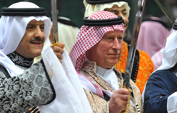 Britain's Prince Charles (C), wearing a traditional Saudi uniform, dances with a sword during the a traditional Saudi dancing, known as 'arda', which was performed during Janadriya culture festival at Der'iya in Riyadh, February 18, 2014. REUTERS/Fayez Nureldine/Pool (SAUDI ARABIA - Tags: POLITICS ROYALS) - RTX192RF