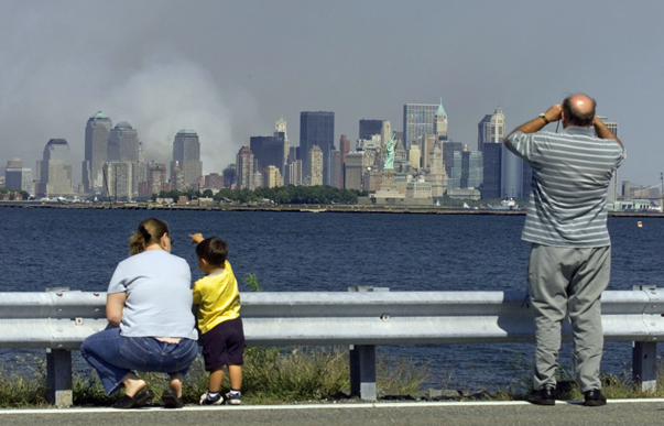 Bystanders watch the smoke from the remains of New York's World Trade Center as it billows from lower Manhatten as the Statue of Liberty (C) stands guard in a photograph taken across New York Harbor from Jersey City, New Jersey September 12, 2001. Each of the twin towers were hit by hijacked airliners and collapsed in one of numerous acts of terrorism directed at the United States September 11. REUTERS/Ray Stubblebine RFS - RTRMNBB