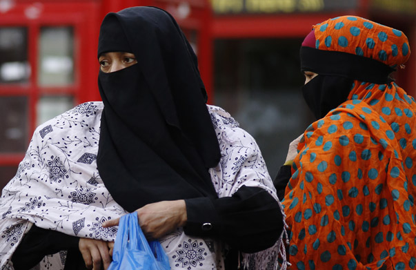 Women wears a full-face veil as they shop in London September 16, 2013. As the British government considers how to better integrate Britain's 2.7 million Muslims without restricting the right to freedom of religious expression, it has steered clear of following the examples of France and Belgium, where it is illegal for women to wear full-face veils in public.  There have been growing calls from some British lawmakers for a ban on veils in schools, but women wearing headscarves and veils on the streets of east London, home to a large Muslim community, said the government should not get involved in religious matters.  REUTERS/Luke MacGregor (BRITAIN - Tags: SOCIETY RELIGION) - RTX13NPK